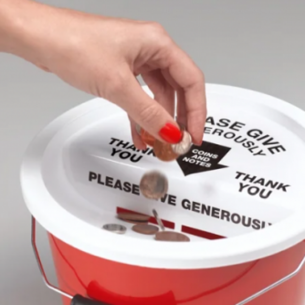 A hand wearing red nailpolish placing coins into a donation bucket.