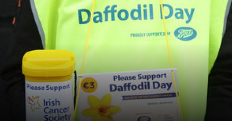 A volunteer in a hi-vis vest collects money for Daffodil Day.