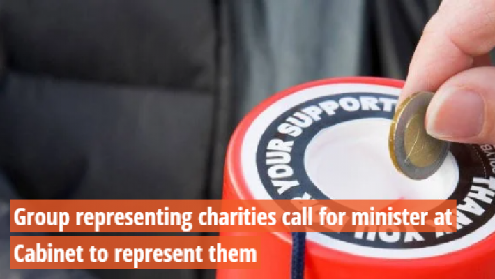 Hand putting coin into donation bucket.