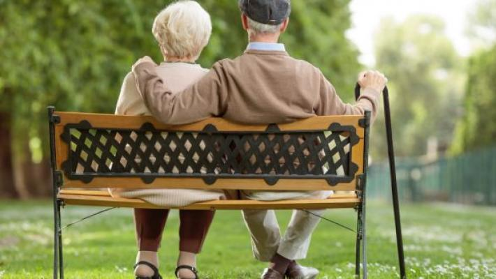 Two older people sitting on a bench, viewed from the back.