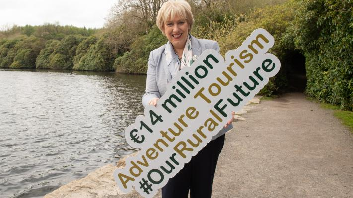 "Heather Humphreys holding a sign that reads, ""€14 million Adventure Tourism #OurRuralFuture""."