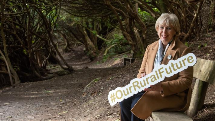 Minister Heather Humphreys holding a #OurRuralFuture sign. She is seated in front of a woodland background.