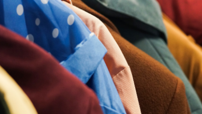 An image of some coats hanging on a rack.